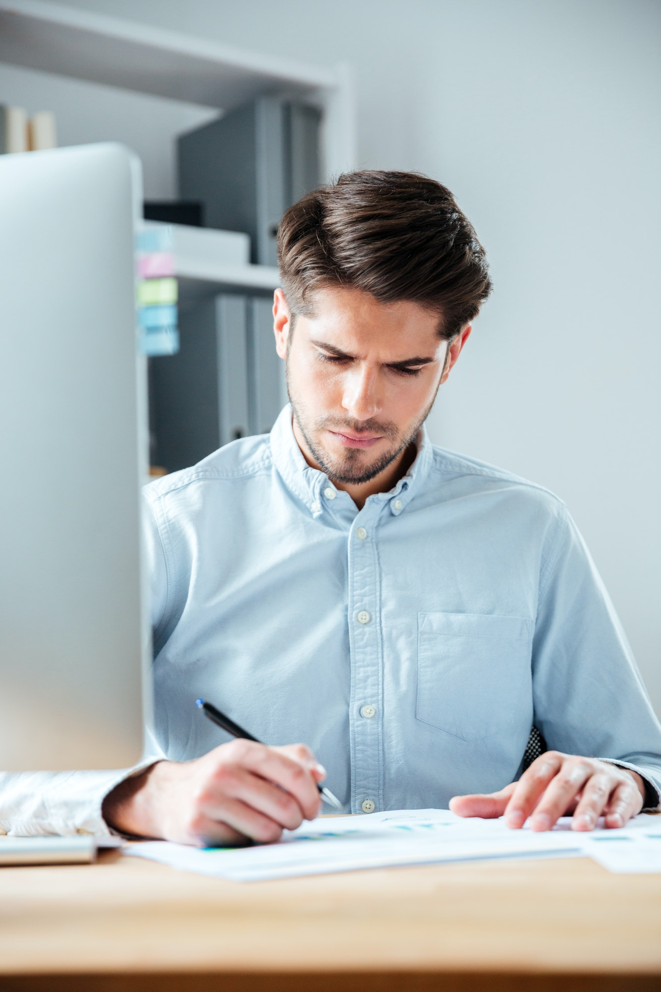 Confident businessman sitting at the table and signing document